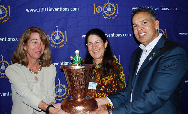 Dr. Diane Perlov (center) and William Harris (right) present the Scribe Clock to Kathryn Kean of National Geographic